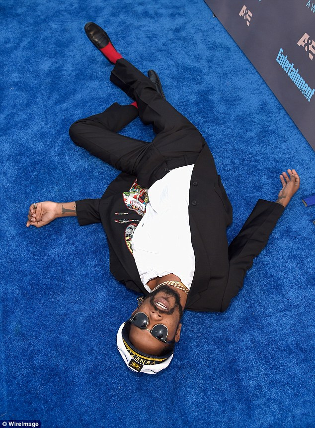 Ready for his close up: The Straight Out Of Compton star threw himself down on the unusual coloured red carpet and pose for snaps lying down