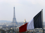 file - In this April 1, 2016 file photo, the French flag above the skyline of the French capital with the Eiffel Tower, The Invalides Dome and roof tops are seen from the colonnade of the Pantheon Dome in Paris. The Eiffel Tower, normally open every day of every year, is closed Tuesday Dec.13, 2016 because of a strike over salaries and working conditions. (AP Photo/Francois Mori)