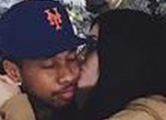 Kylie snuggles with Tyga under her Christmas tree