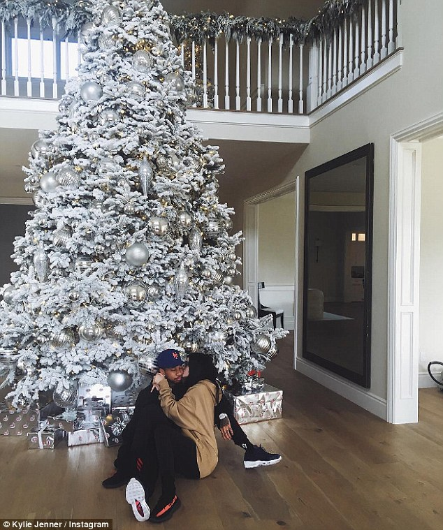 Festive fun: Kylie Jenner snuggled under her Christmas tree with boyfriend Tyga in an Instagram snap she shared on Wednesday