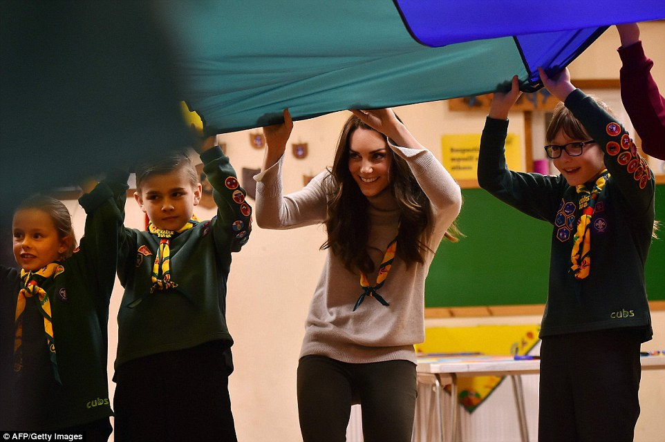 Peek-a-boo! Kate, casually dressed in skinny jeans and a turtleneck jumper, peers out from below the parachute