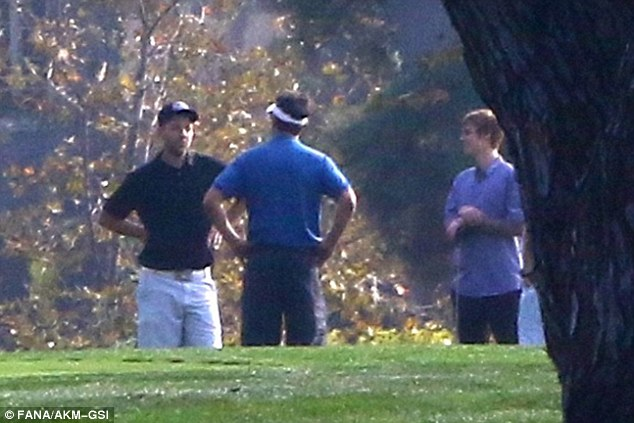 Guys' day:A third man was spotted with the group out on the golf course, wearing a bright blue polo shirt with dark shorts and a white visor