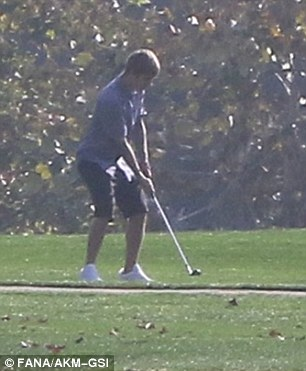 Casual day: Justin practiced his swing and chatted while sipping a beverage out on the course