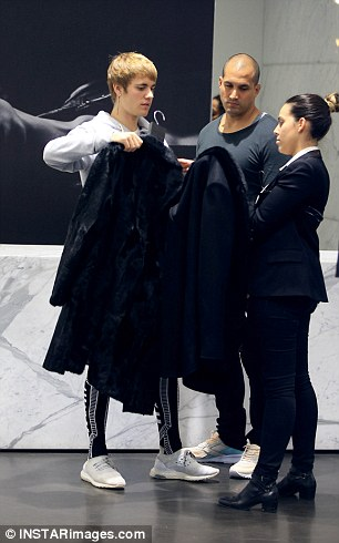 High profile: The performer received the star treatment from the staff at Yves Saint Laurent in Beverly Hills as he tried a black pea coat on for size on Tuesday