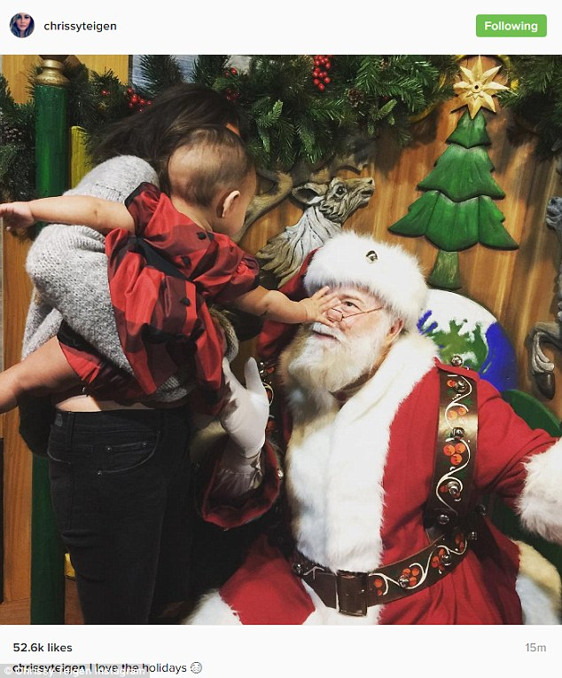 Hello Santa! One of the photos Chrissy shared was of her holding little Luna, who reached out to touchSaint Nick's face