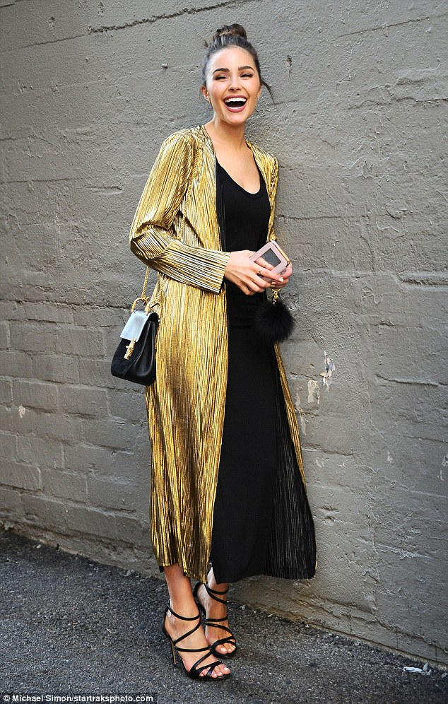 Eye-catching: On Wednesday, Olivia Culpo was seen strolling through an alleyway in Los Angeles in a glimmering gold overcoat