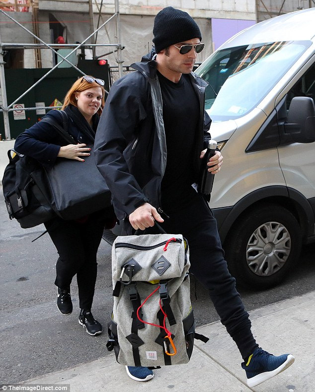 Looking good: Zac donned a black jacket with a matching T-shirt, joggers and a beanie while toting a backpack