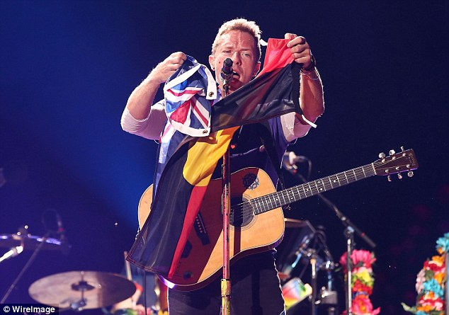 Waving them high: The acclaimed group certainly put on an energetic performance and at one point, Chris brandished an Aboriginal flag and an Australian flag
