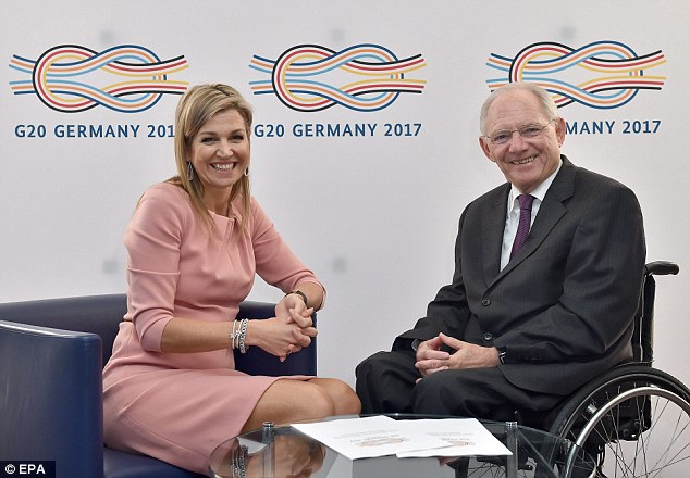 The royal later removed her jacket to showcase a more demure rose dress as she met with German Federal Minister of Finance Wolfgang Schaeuble