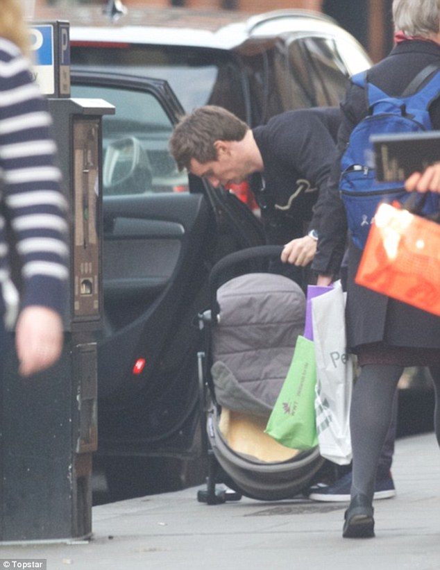He's the man: The 34-year-old Fantastic Beasts star looked every inch the doting dad as he took his six-month-old daughter for a walk around the British capital following his OBE honour