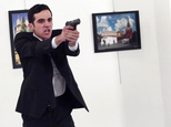 """ADDS THE NAME OF THE GUNMAN - A man identified as Mevlut Mert Altintas holds up a gun after shooting Andrei Karlov, the Russian Ambassador to Turkey, at a photo gallery in Ankara, Turkey, Monday, Dec. 19, 2016. Shouting """"Don't forget Aleppo! Don't forget Syria!"""" Altintas fatally shot Karlov in front of stunned onlookers at a photo exhibit. Police killed the assailant after a shootout. (AP Photo/Burhan Ozbilici)"""