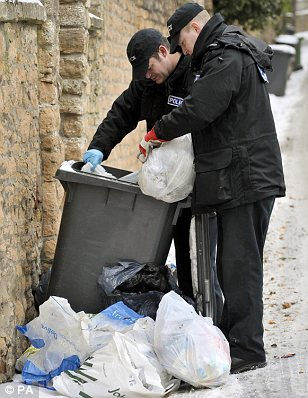 Search: Police examine a wheelie bin near the flat belonging to Jo Yeates