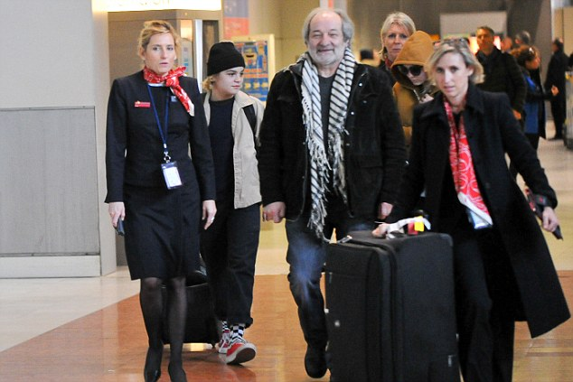 Festive spirit: The family made their way out to a waiting car with the help of airline staff
