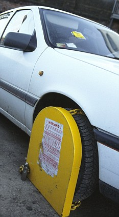 Illegally parked car with wheel clamp placed on front wheel