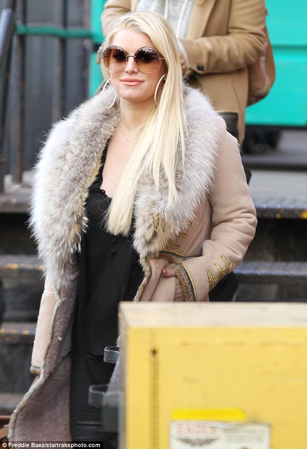 Fresh-faced: The smiling star showed off peach lipstick, and hid her eyes behind a large pair of round-framed sunglasses