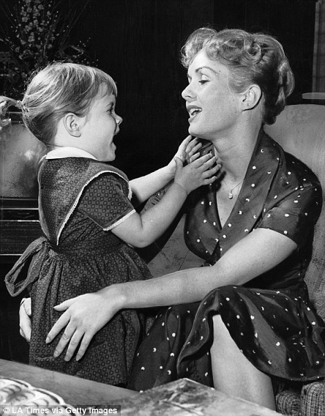 Despite losing her first husband in bitter public humiliation and later suffering two other failed marriages, Reynolds never relented in her love of motherhood. She described Carrie and her brother Todd as the 'lights of her life' until her death. Above, she is seen (left) as a new mother to Carrie in 1956 and (right) greeting her daughter after an afternoon nap in 1959