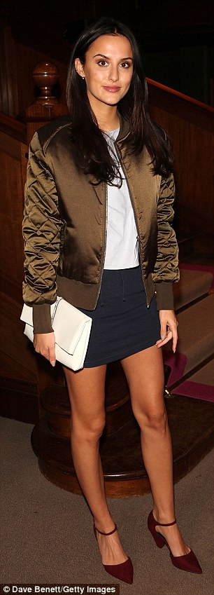 Brunette beauty: She covered her pale blue top with an on-trend khaki bomber jacket and carried her essentials in a classy white clutch