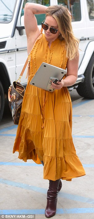 Going country: The Texas native paired a tiered dress with a pair of brown high heel boots