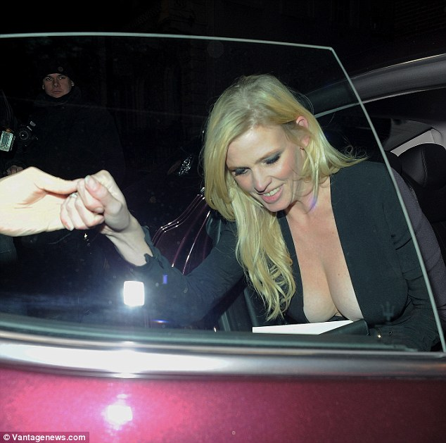 Helping hand: The blonde beauty was given a little assistance as she clambered out of her taxi