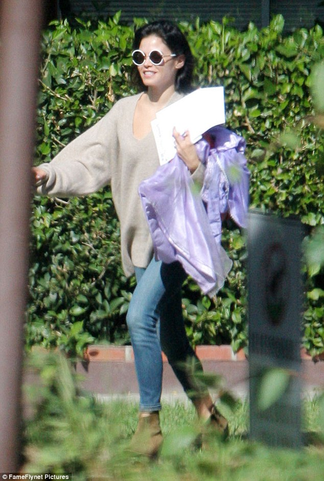 Holiday prep: The 35-year-old was carrying a gleaming purple dress that appeared to be a Halloween costume for her three-year-old