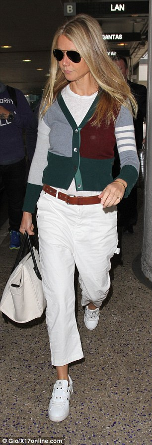 Casually cool: For her flight, the star donned a pair of loose-fit cropped white pants which were chic but comfortable, and added a simple white tee under a patchwork cardigan