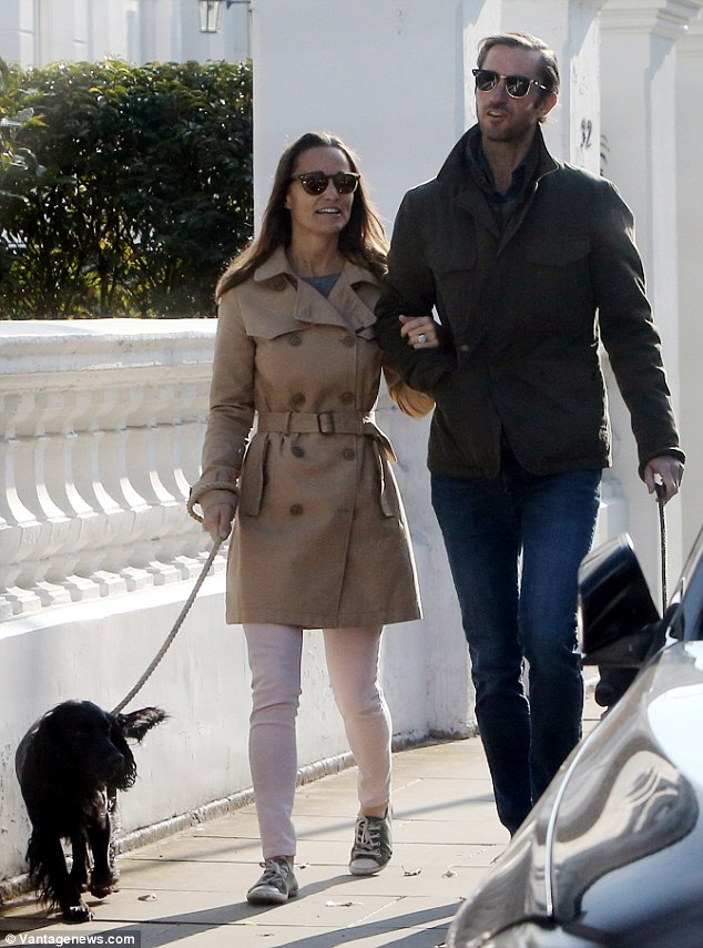 The happy couple strolled arm in arm as they walked their dogs, shielding their eyes from the autumn sun with dark shades