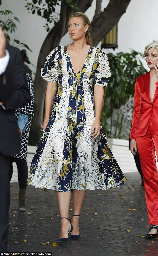 Sweeping: The 29-year-old went for a super high fashion look as she dazzled in a floral gown adorned with stripes of different material extending vertically along the length of the flirty hemmed dress