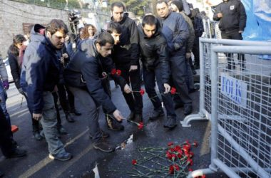 Men lay flowers outisde the Reina nightclub by the Bosphorus, which was attacked by a gunman, in Istanbul