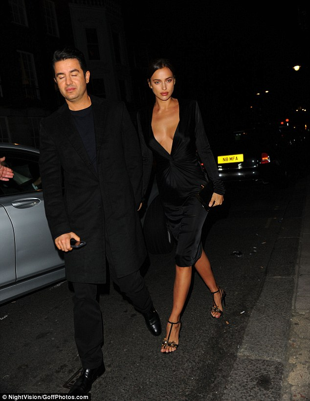 Following his lead: Irina made her way to the venue holding hands with a male pal