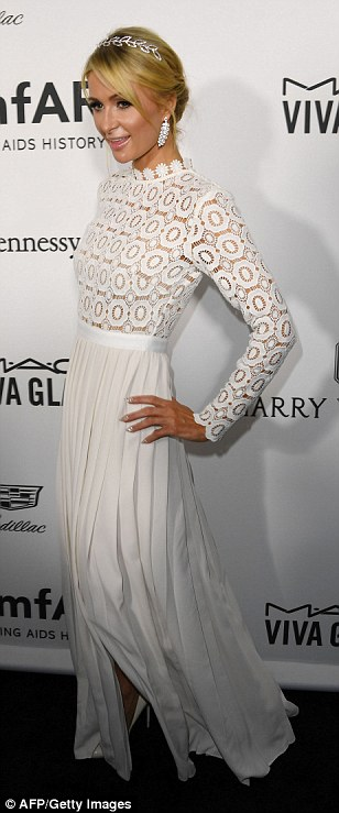 Wowing in white: Paris posed up a storm for the cameras in her statement white gown with a flowing pleated skirt