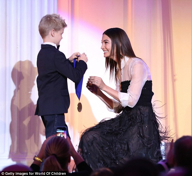 Honoured: Lily knelt down to accept her award from one of the children on stage