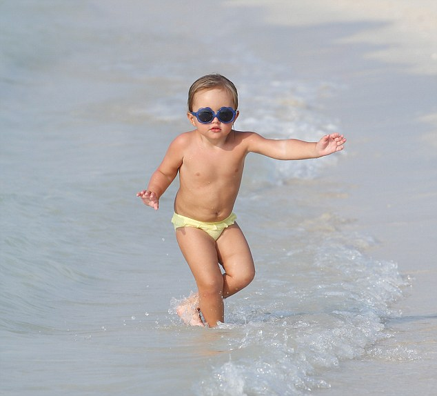 Her mini me:Little Sophia looked on cloud nine as she giggled with her mum, running around in a pair of yellow bikini bottoms and mini shades