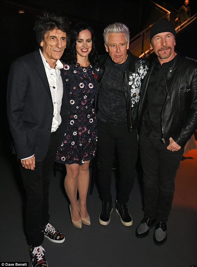 Pretty petal: Sally (pictured with Ronnie, The Edge and Adam Clayton) looked effortlessly stylish in a black floral-print dress, which featured sparkling sequinned detailing