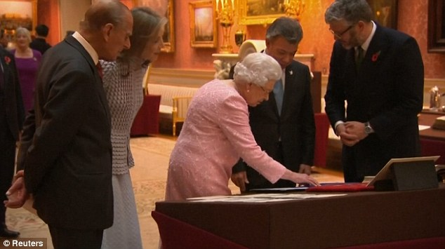 The Queen leans over the display of British currency, including the new £5 note, and explains how it is different to the old paper note