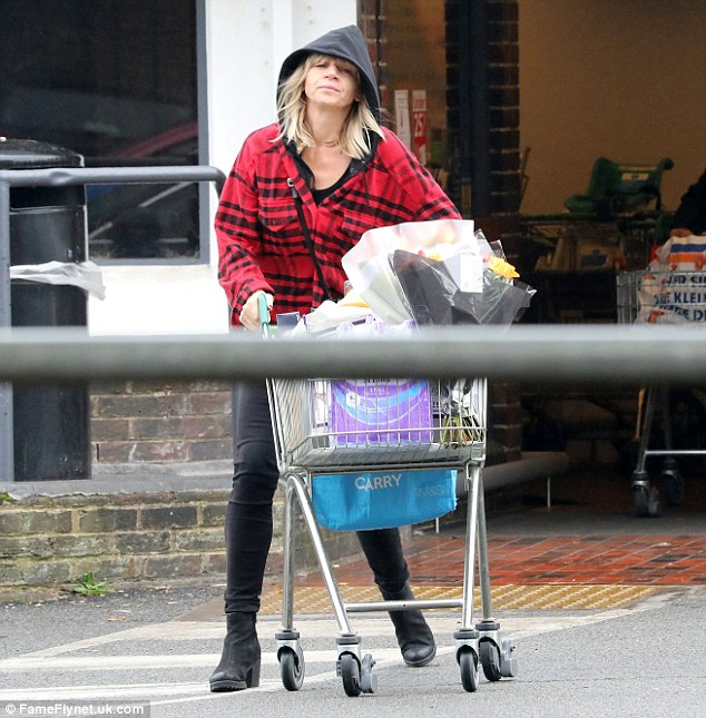 Going solo: Newly-single Zoe Ball, 45, went make-up free as she emerged from Waitrose in Brighton with a trolley full of groceries on Saturday