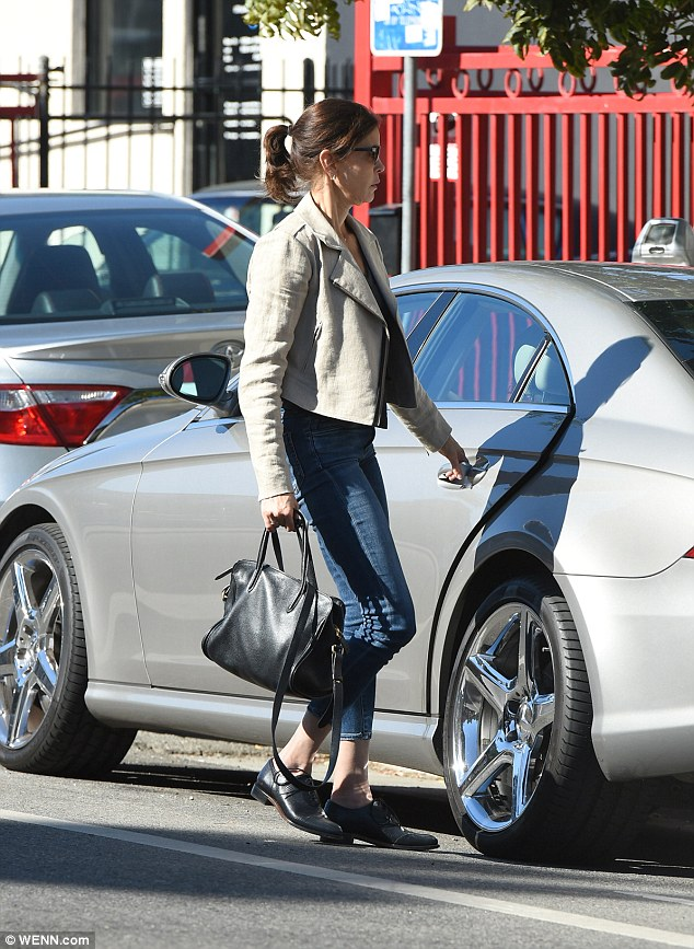 Relaxed: The former NFL cheerleader was casually clad in a cream leather biker jacket and jeans