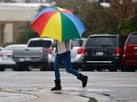 A pedestrian shields herself from freezing rain in downtown Bartlesville, Okla., Friday,  Jan. 13, 2017. An ice storm is expected to hit the area today.   A winter storm that pounded northern California is descending upon the southern Plains, packing crippling ice accumulations and heavy rain that could cause widespread power outages and flooding.  (Mike Simons/Tulsa World via AP)