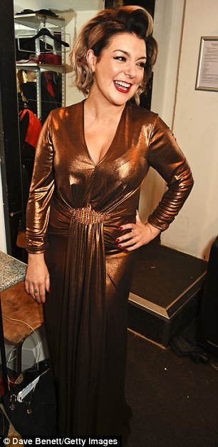 Going for gold: Sheridan shimmered beneath the backstage lights as she modelled her striking dress on Thursday evening