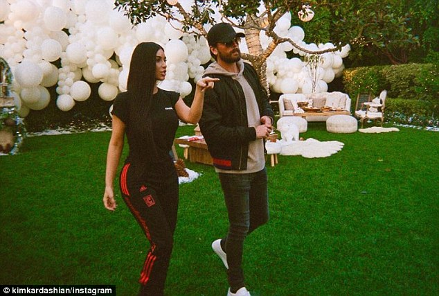 'On our way #Dubai' : Kim wore the Adidas Calabasas bottoms with a black Henley top and a red and black jacket; pictured with Scott Disick