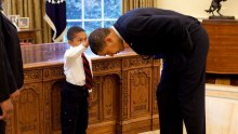 A White House staffer's son touches Barack Obama's head in the Oval Office