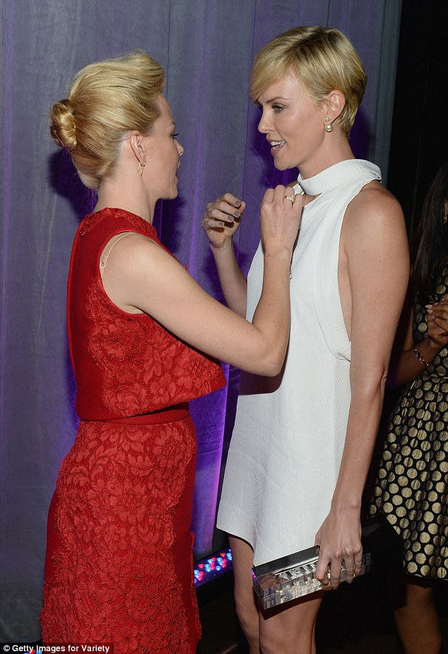 Helping out: The star stopped to chat to other nominee Elizabeth Banks, who appeared to take a closer look at Charlize's cut before helping the actress cover it up