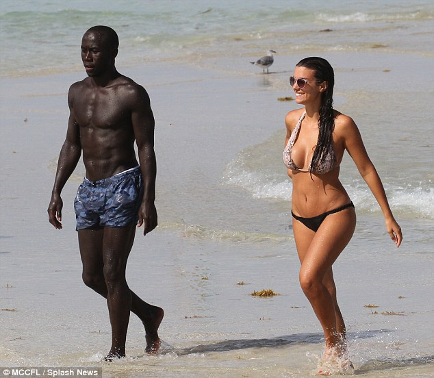 Bacary Sagna and his wife Ludivine enjoy a sun-kissed stroll across the beach in Miami