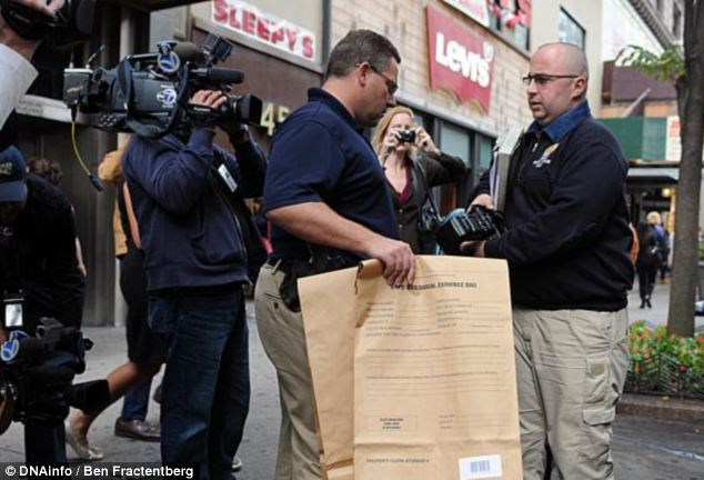 Found: Investigators remove evidence bags containing the male fetus from the scene on Thursday