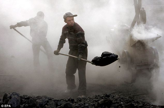 A cloud of dust and dirt engulfs a group of Chinese workers shoveling coal at a coal mine in Yaojie, Gansu province, China, 01 December 2007.