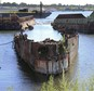 FILE - In this Aug. 22, 2016 file photo, rusting remnants of an old Russian submarine, used as a set for a Harrison Ford movie and as a floating museum until sinking during a 2007 nor'easter, sits rusting in a scrapyard in the Providence River in Providence, R.I. State environmental officials sued to have the sub and several other vessels removed from the river. A state superior court judge ordered Rhode Island Recycled Metals LLC in December to begin removing the vessels from the river. The permitting process is underway. (AP Photo/Jennifer McDermott, File)