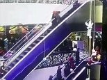 The woman is captured at the top of the escalator in the dark dress as she begins to stumble