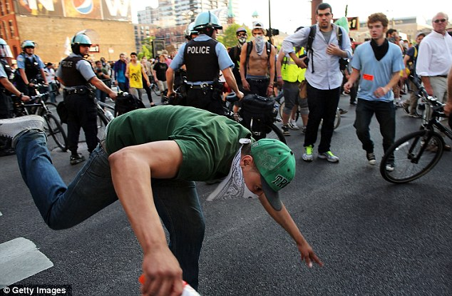 A protester trips after falling over a police officer during a demonstration by Occupy Chicago and other groups in downtown Chicago on the eve of the NATO summit on May 19, 2012