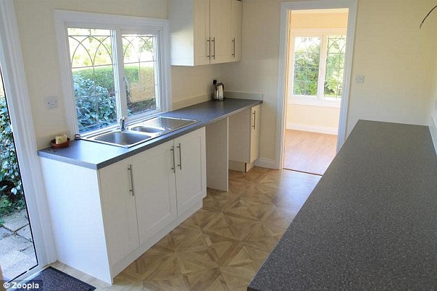 The new kitchen includes decorative vinyl flooring, a tile splashback and white cabinets