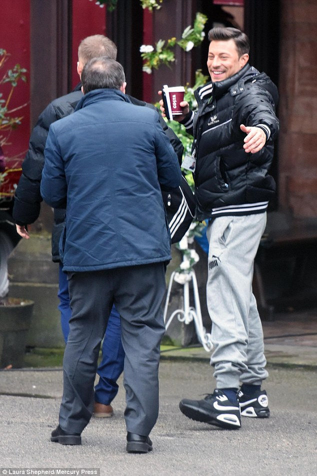 Happy days: Her handsome co-star Duncan James - who plays adulterer Ryan Knight - looked in high spirits as he made his way on set, cradling a cup of coffee