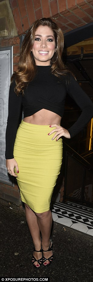 Turning heads:Making the most of her well-sculpted stomach, the brunette beauty added a zingy yellow skirt that clung to her toned legs
